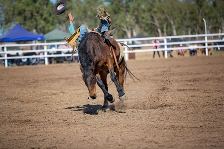 Cowboy is falling off his ride on bucking horse in bareback bronc event at a country rodeo and loses his hat. Stock Photo