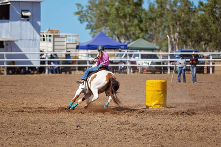 A cowgirl competing in a barrel racing competition at a country rodeo