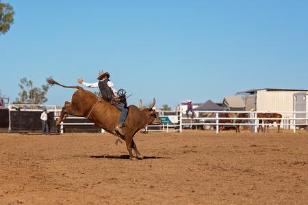 Ein Cowboy, der an einem Bullenreitereignis bei einem australischen Landrodeo teilnimmt
