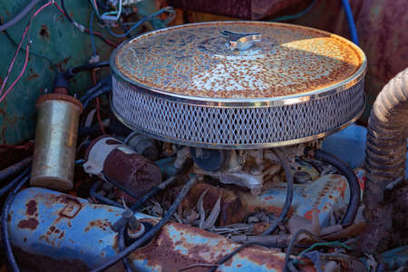 Close up of the old rusted motor of an abandoned car