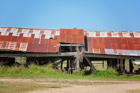 A long low decrepit old shed with rusted iron roof against a blue sky background