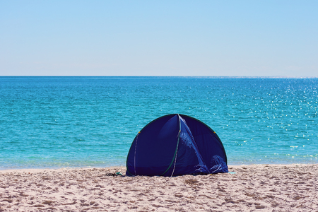 A small blue round collapsible shade tent on the white silica sand of Whitehaven Beach in the Whitsunday Islands of Australia
