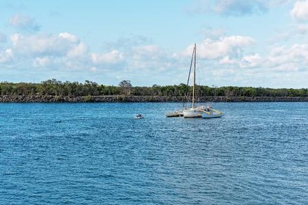 Owner motoring in small boat towards his moored catamaran in river Editorial