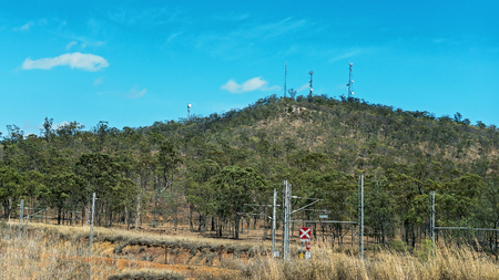 Railway infrastructure on electric lines to transport coal from mines to port with communication towers on hill Stock Photo