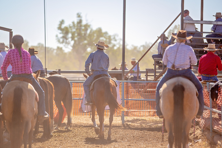 Cowboys waiting in holding area to take their turn on horseback in camp drafting competition at a country rodeo Stock Photo