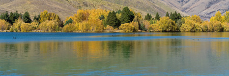 A scenic lake with yellow autumn foliage on the trees on the banks adding beautiful reflections to the calm water