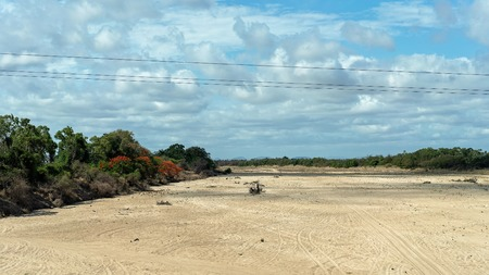 A dry creek bed with no water during a drought, as seen from a bridge with power lines in the foreground and blue cloudy sky Фото со стока