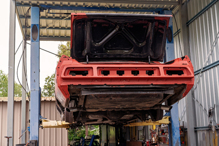 Back of an old car on a hoist being restored in a garage Фото со стока
