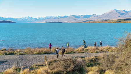 LAKE TEKAPO, NEW ZEALAND - April 2018: The beauty of the majestic alps on the glacial shores of Lake Tekapo attract tourists in their thousands each each. 16th April 2018.