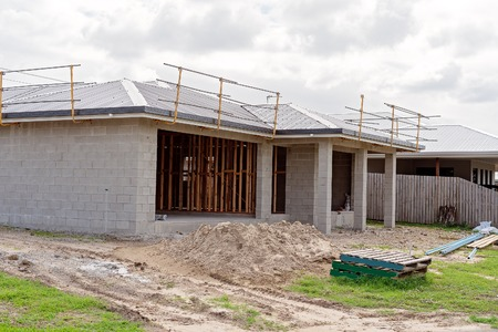 A residential home being built of concrete block with a black steel roof