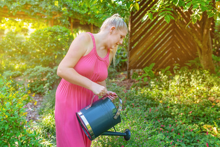 Young blonde woman in pink dress watering plants in a garden in late afternoon light