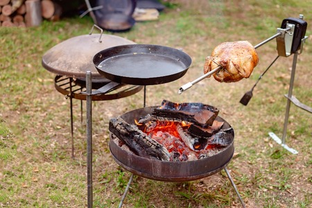 A chicken roasting on a rotisserie over an outdoor barbecue fire Stock Photo
