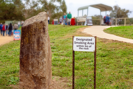 Designated smoking area signage next to a rock at a bush festival