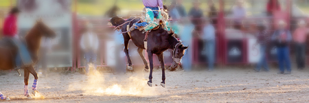 Bucking bronc horse riding competition entertainment at country rodeo Фото со стока - 120672746