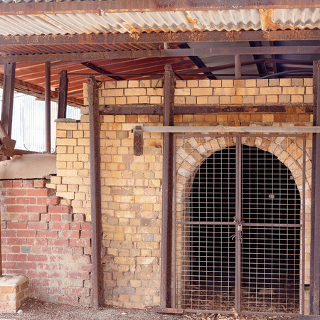 An old disused brick pottery kiln closed off by a fence now, but once used to fire earthenware, stoneware and porcelain