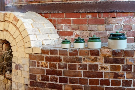 Pottery household containers sitting on a brick wall beside an old kiln from yesteryear