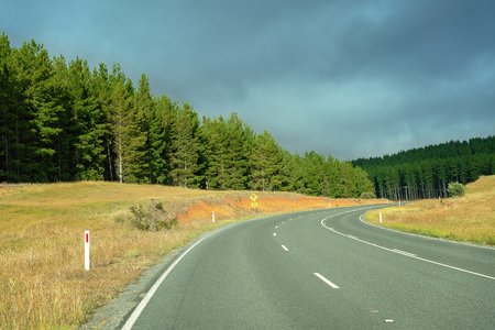Long curving Australian highway through pine forest and mountains beyond