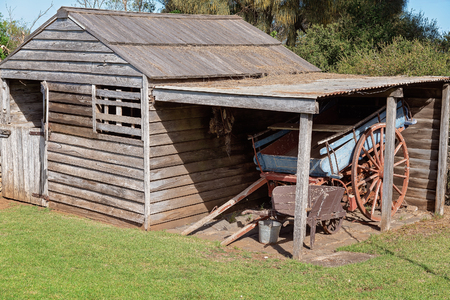 An old timber shed shelters a vintage horse drawn wagon and wheelbarrow from yesteryear - Australia