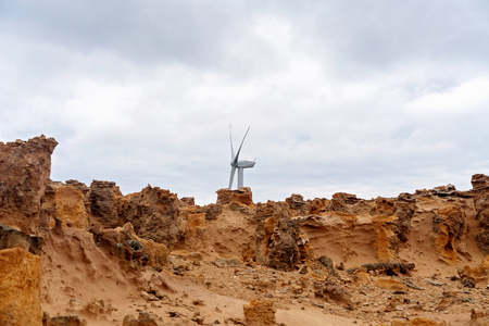 A modern wind farm turbine contrasting starkly with the ancient petrified forest on Victorias coastline - Australian tourist attraction Great Ocean Road