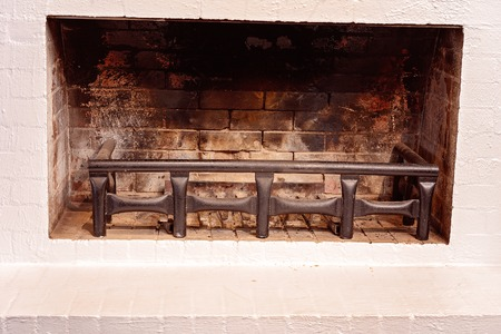 An unlit fireplace surrounded by white painted bricks gives a feeling of welcome and warmth Reklamní fotografie - 121796069