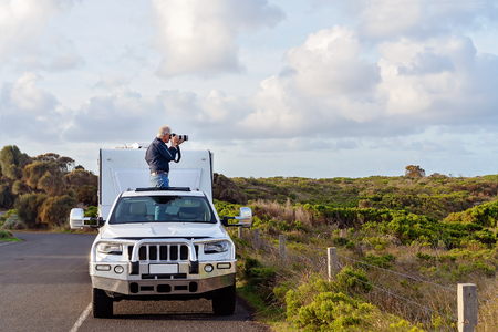 Male retiree on caravan holiday taking photos out of car sunroof on The Great Ocean Road Australia Foto de archivo - 122138918