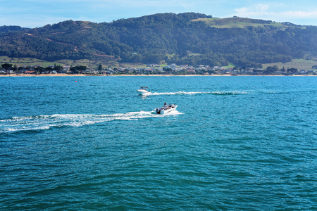 Motor boats going to and from a marina for fishing activities on a beautiful calm sea