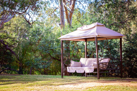 A comfortable swing chair under cover in a beautiful outdoor lush garden setting at an Australian country holiday resort