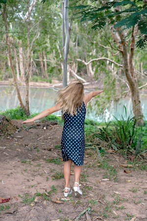 A young blond girl in a spotted dress on a creek bank, having fun twirling around so that her hair is a blur around her face making her unidentifiable.