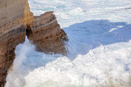 Waves crashing around the limestone rock formations on The Great Ocean Road Australia, a well known tourist destination