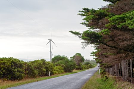 New generation wind turbines beside a forested road in the Australian countryside of Victoria