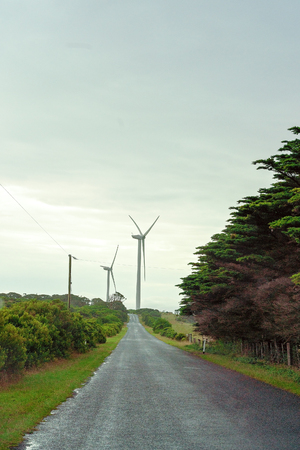 New generation wind turbines at the end of long straight forested road in the Australian countryside of Victoria