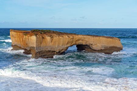 The limestone rock formations on the scenic coastline of Australia's Great Ocean Road - London Bridge Фото со стока