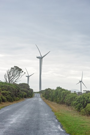 Modern wind turbines generating power at the end of a long straight road on the coastline of Australia Stock fotó