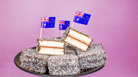 Traditional Australian lamingtons, individual cakes filled with jam, iced and rolled in coconut. Favorite food on Australia Day and Anzac Day, served with the countrys flag for the patriotic.
