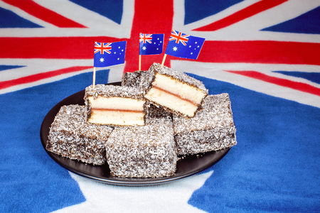 Australian lamingtons with tiny flags on toothpicks on a background of the country's flag 免版税图像