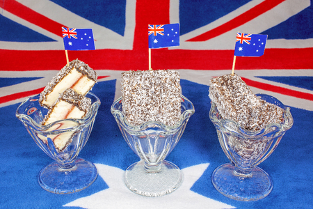 Tiny flags on Australian lamingtons in glass jars on a background of the countrys flag Фото со стока