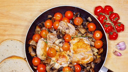 Chicken thighs browned in a frying pan with mushrooms, cherry tomatoes, garlic and thyme, and sprinkled with balsamic vinegar