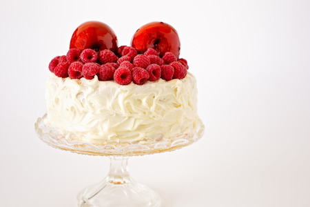 Red toffee apples and raspberries on top of a creamy frosted cake on a glass stand with a white background. Copy space for text.