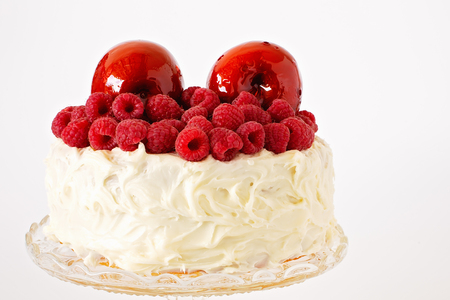 Red toffee apples and raspberries on top of a creamy frosted cake on a glass plate isolated on a white background. Copy space for text. Фото со стока