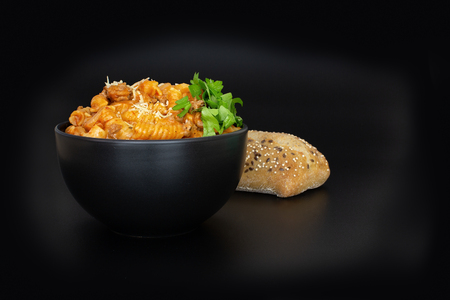 A simple bowl of pasta bolognese sprinkled with cheese and parsley, accompanied by crusty bread on a black background