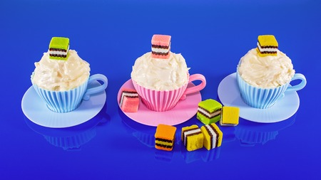 Colorful cupcakes on a bright blue background, baked in a cup and decorated with candy for childrens, teens birthday or holiday celebration
