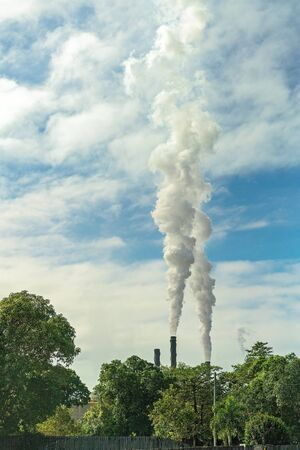 Smoke rising into the sky and polluting the atmosphere from a sugar mill refinery in Australia as it processes the harvested crop from surround farmland Фото со стока
