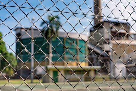 Dirty old chain link fence keeping people from entering a sugar cane mill refinery in Australia