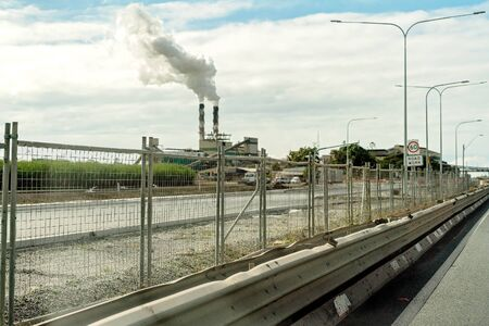 Construction of a highway in an Australian country town to bypass the city and facilitate an improved traffic flow, sugar mill refinery in the background