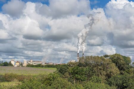 An Australian sugar mill refinery in production as it processes sugar cane from surrounding farmland in north Queensland and produces smoke from its chimneys Фото со стока