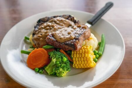 A typical Aussie pub meal of steak with peppercorn sauce and vegetables served in an Australian hotel Foto de archivo