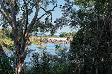 A weir or small dam used to prevent flooding, measure water discharge, and help render this Australian country river more navigable by boat Фото со стока