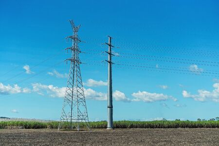 High tension power poles against a background of blue sky and an agricultural field of sugar cane