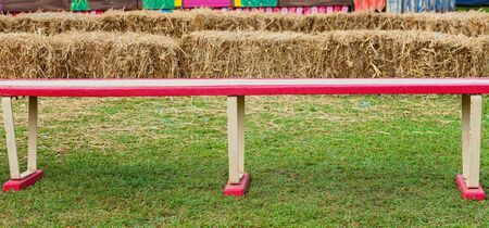 A colorful wooden bench seat on green grass at a country fair with hay bales in the background Фото со стока