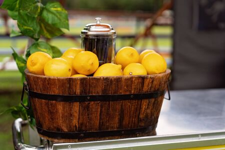 A barrel of lemons on a fresh lemonade for sale stand at a country fair